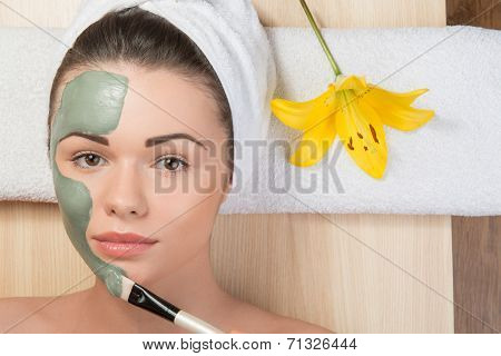 Beautiful girl with a towel on her head applying facial clay mas