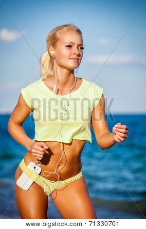 Woman running with earphones on sea background. Caucasian beautiful fitness girl working out on summer