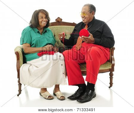 A laughing senior couple sitting on a sofa while she starts a crochet project.  They're wearing Christmas colors.  Isolated on white