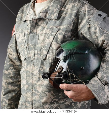 Closeup of an American Airman in camouflage fatigues holding a flight helmet under one arm, Square format, man is unrecognizable.