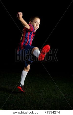 Low Key Portrait Of A Boy Kicking A World Cup Football