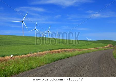 Wind mills on rolling hills and dirt road in Palouse, Washington