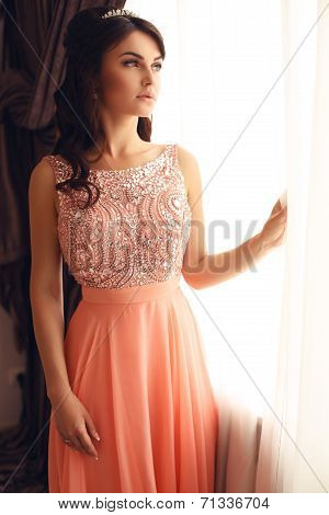 Beautiful Woman With Dark Hair In Elegant Coral Dress With Diadem