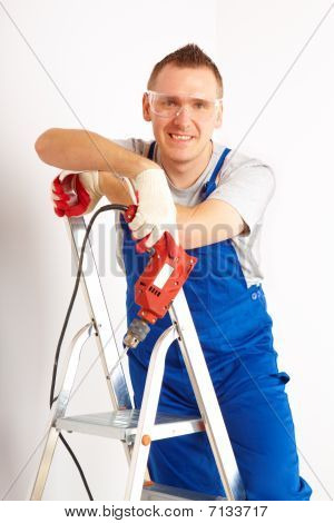 Man With Drill Standing On Ladder