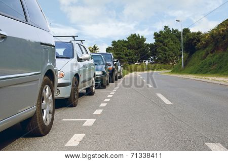 Cars Parked On The Side Of An Empty Road