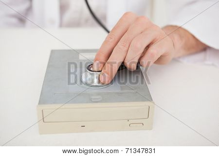 Computer engineer listening to harddrive with stethoscope in his office