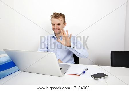 Happy businessman video conferencing on laptop in office