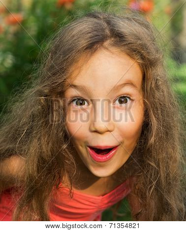 Cute Little girl in red dress is suprised and so happy about it