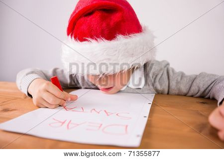 Child writing letter to santa at the desk