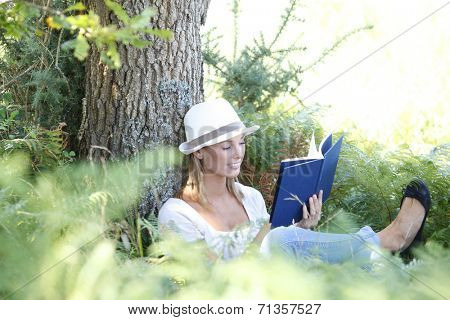 Woman in park enjoying novel