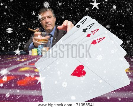Gambler holding whiskey at poker table with digital hand of cards in foreground against snow