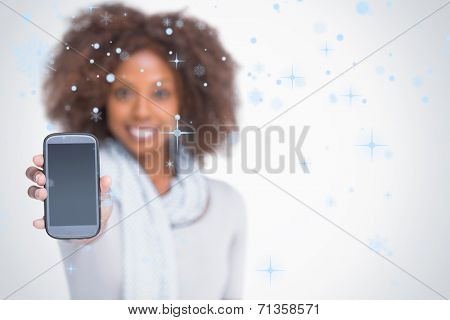 Woman with afro showing her smartphone against snow falling