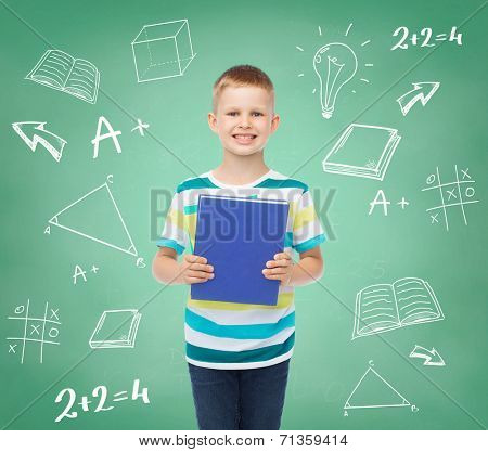 education, childhood and school concept - smiling little student boy with book over green board with doodles background