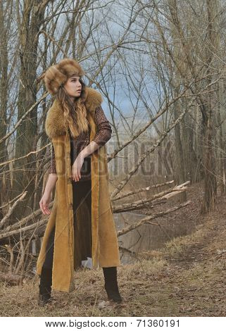 Fashion beauty girl in fur coat standing in nature background in early spring