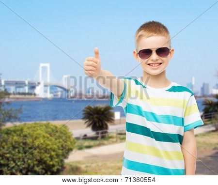 happiness, summer, childhood, gesture and people concept - smiling cute little boy in sunglasses showing thumbs up over city background