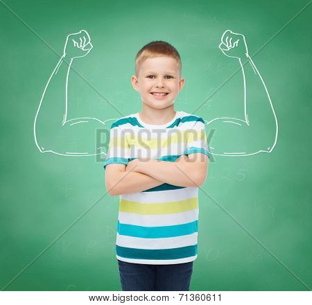 happiness, childhood, school, education and people concept - smiling little boy in casual clothes over green board background strong arms drawing