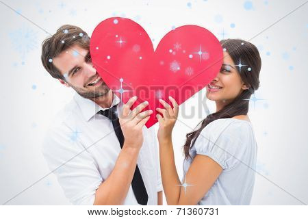 Couple smiling at camera holding a heart against snow falling