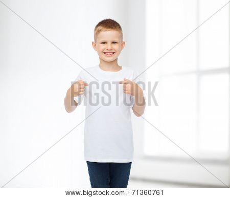 advertising, people, gesture and childhood concept - smiling boy in white blank t-shirt pointing finger himself over white room background