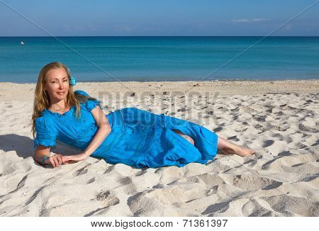 The young woman in a romantic dress lies on sand near the sea Cuba Varadero