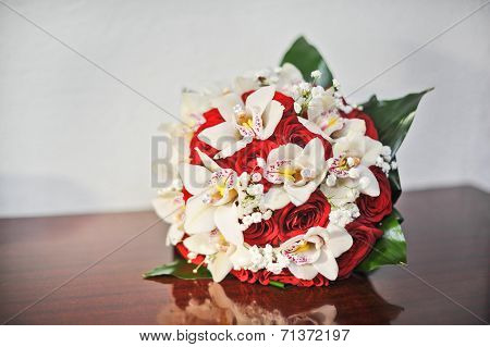 Beautiful bouquet of rose flowers, on table. Wedding bouquet of red roses. Elegant wedding bouquet