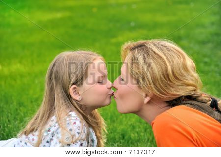 Mother is kissing her daughter