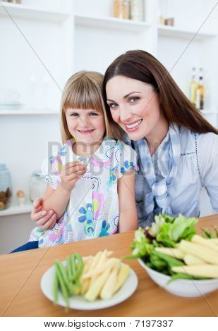 Cheerful Little Girl Eating Vegetables With Her Mother