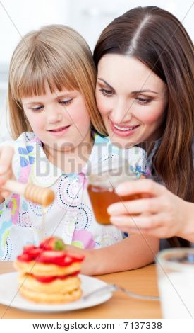 Joyful Mother And Her Daughter Putting Honey On Waffles