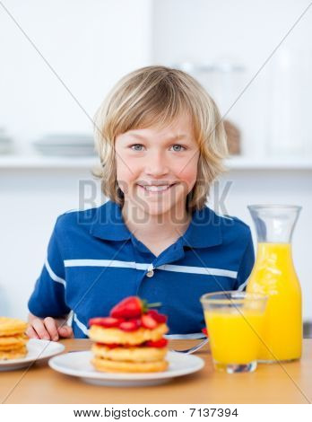 Smiling Boy Eating Waffles With Strawberries