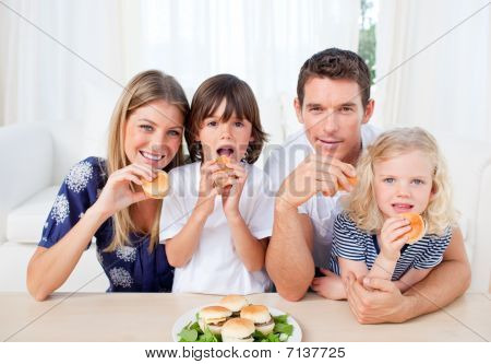 Enthusiastic Family Eating Burgers In The Living Room