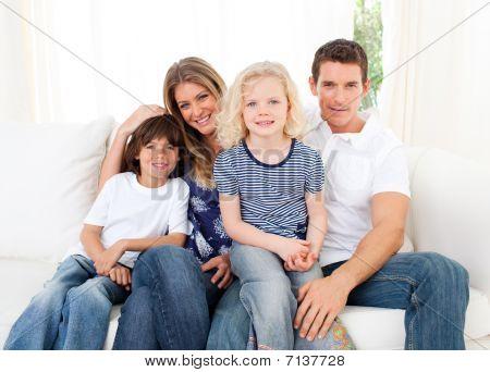 Joyful Family Watching Television Sitting On Sofa