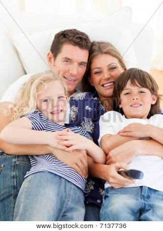 Caucasian Family Watching Television Sitting On Sofa