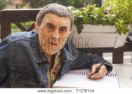 Elderly disabled man with cerebral palsy writing in a notebook at an outdoor cafe.