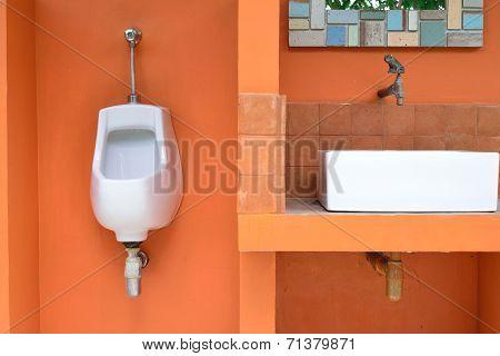 Single Urinal On Orange Wall In Public Toilet