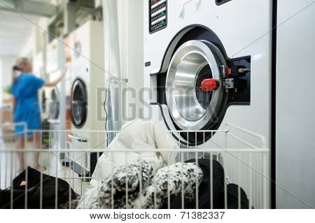 Laundry equipment and female worker on background
