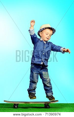 Portrait of a cute little boy in jeans clothes standing on a skateboard. Fashion. Childhood.