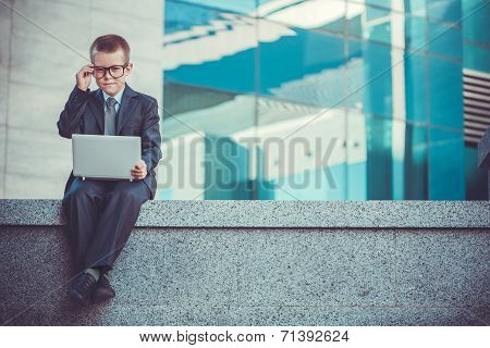 kid businessman with laptop on the blue modern background