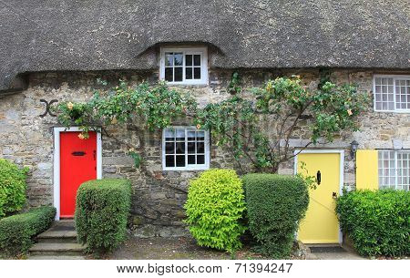 Cottage With Straw Thatched Roof And  Colorful Doors