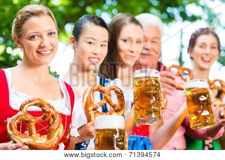 In Beer garden - friends, man and women in Tracht, Dirndl and Lederhosen drinking a fresh beer in Bavaria, Germany