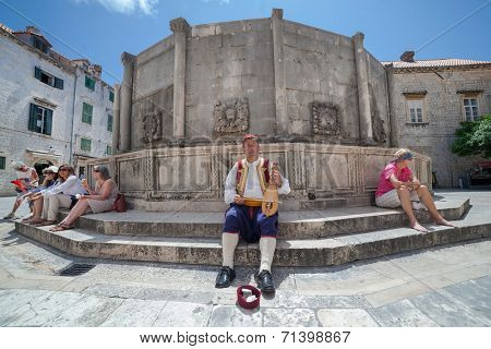 DUBROVNIK, CROATIA - MAY 27, 2014: Man wearing traditional clothes playing lijerica in front of Onofrio's fountain. Lijerica is traditional 3 strings pear shaped instrument from Dalmatian region.