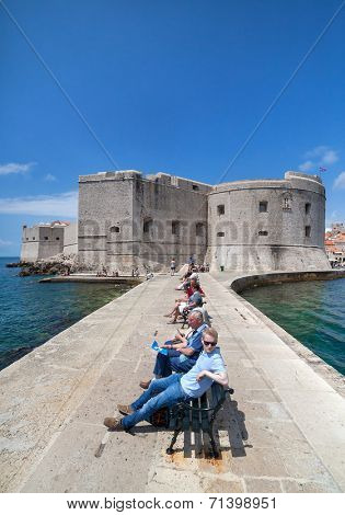 DUBROVNIK, CROATIA - MAY 27, 2014: Tourists sitting on bench on dock in front of the St. John fortress near the old port. Fortress houses the Maritime Museum and the aquarium.