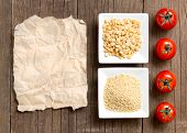 stock photo of millet  - Millet and yellow peas tomatoes and paper on wooden table - JPG