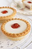 image of tarts  - Cherry Bakewell tart a frangipane pastry covered in almond icing and a half cherry on top - JPG