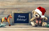 stock photo of teddy  - nostalgic christmas decoration with antique toys teddy bear and wooden rocking horse - JPG
