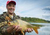 foto of fish pond  - Happy smiling fisherman holding his trophy carp  - JPG