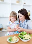 Annoyed Blond Girl Eating Vegetables With Her Mother