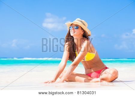 long haired girl in bikini  and a hat on tropical barbados beach
