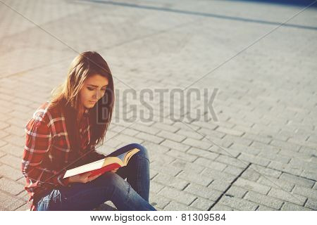 Side view portrait of attractive young girl enjoying a good book sitting at sunny evening outdoors