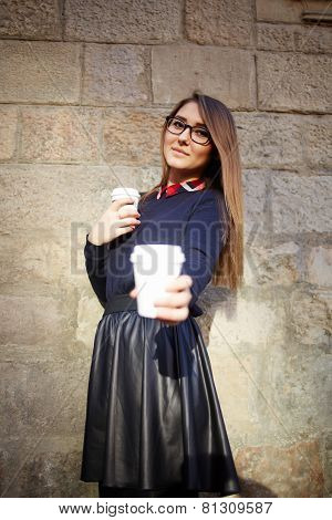Charming young woman offering you a cup of coffee or tea towards the camera