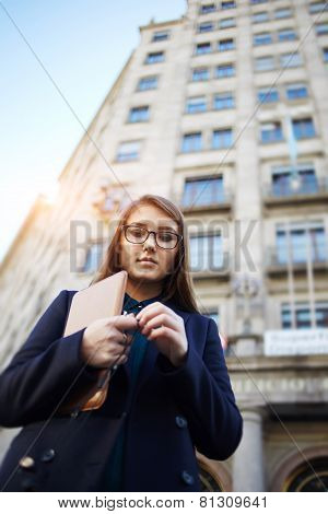 Portrait of elegant young woman standing in the urban setting looking pensive and upset