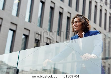 Shot of a happy handsome executive in a suit standing in a city setting